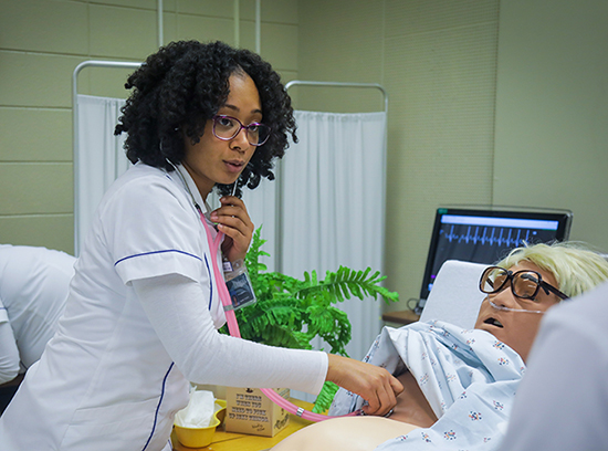 african american nurse practicing on an adult dummy