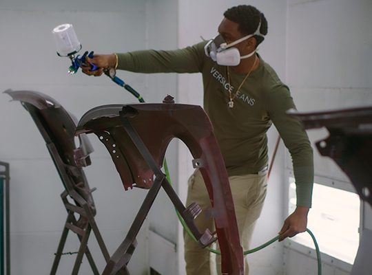 student painting a car door