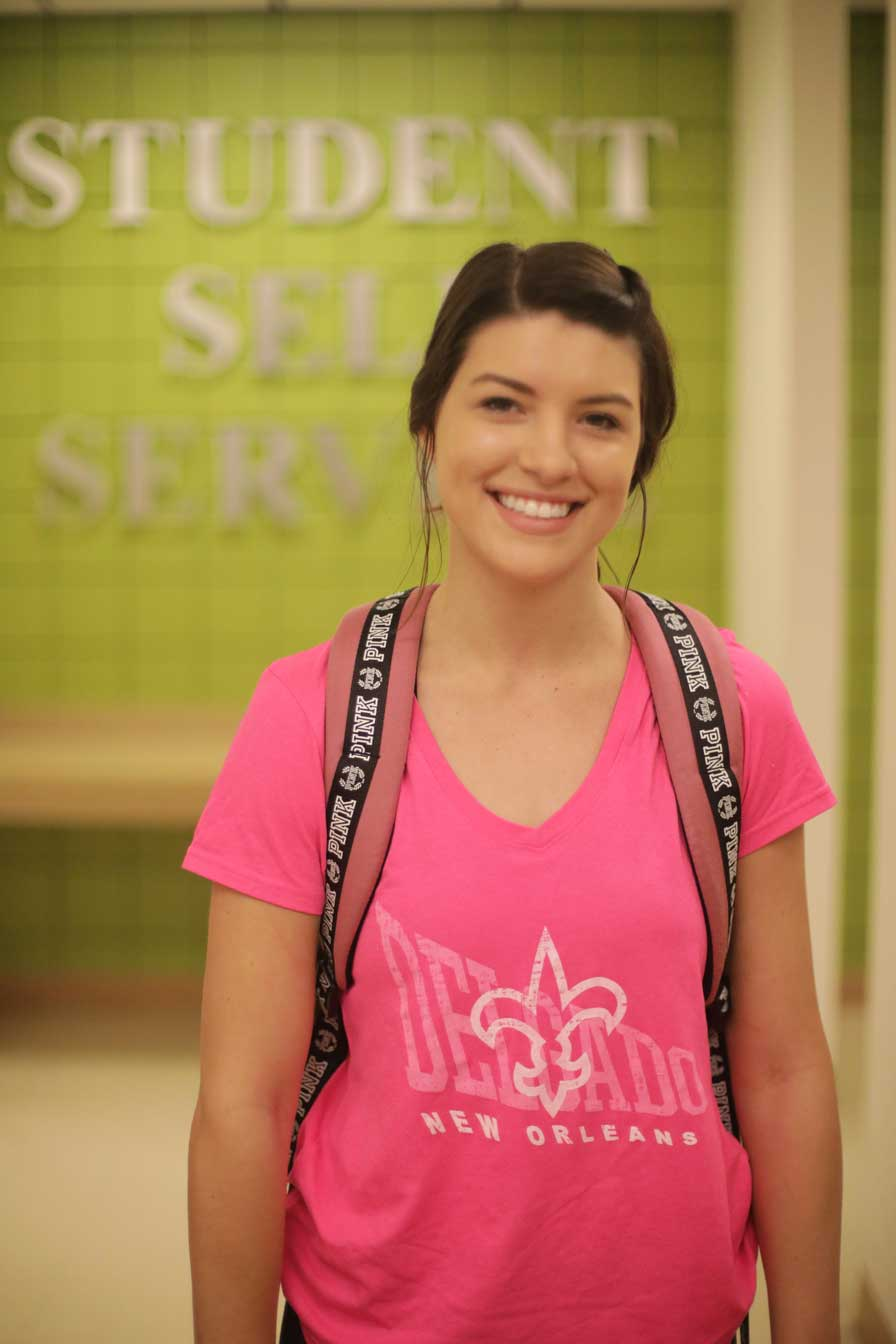 "A Delgado student wearing a pink shirt smiles in front of a wall that says ""Student Self Service"""