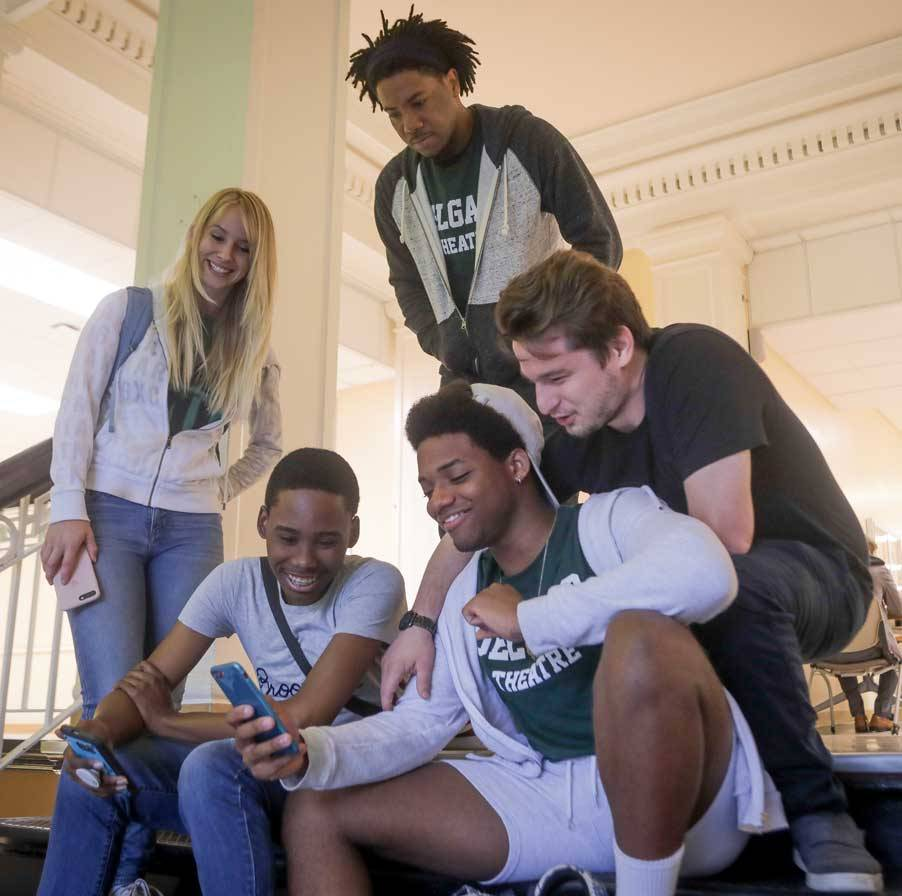 A group of five Delgado students laugh as one student shows off the contents of his cell phone screen.